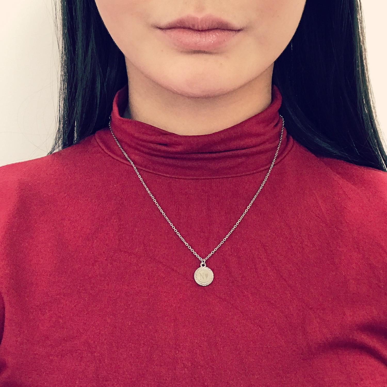 Meisje draagt zilveren ketting met vintage muntje gegraveerd