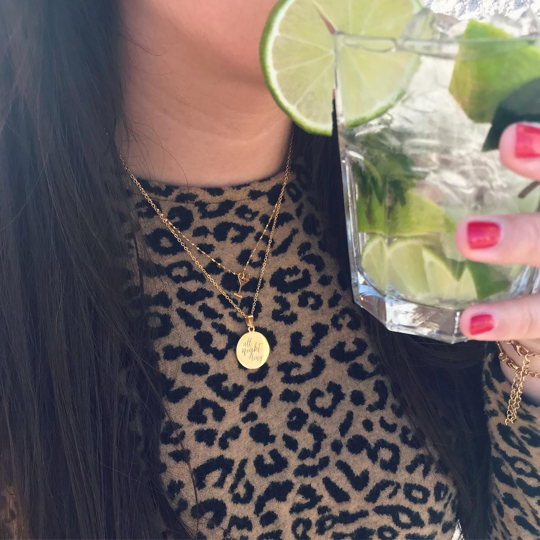 Meisje draagt gouden quote ketting met cocktail