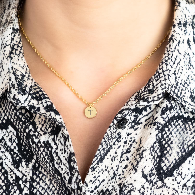 Meisje draagt gouden initialen ketting