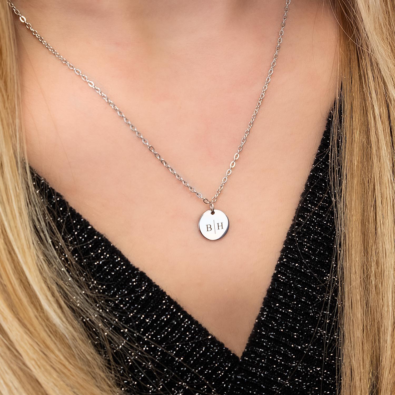 Vrouw draagt zilveren initialen ketting om bij