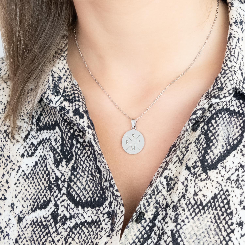 Meisje draagt grote munt met initialen ketting