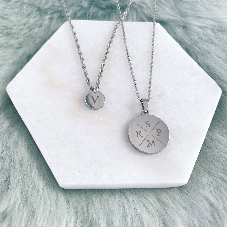 Twee zilveren initialen kettingen op marmer