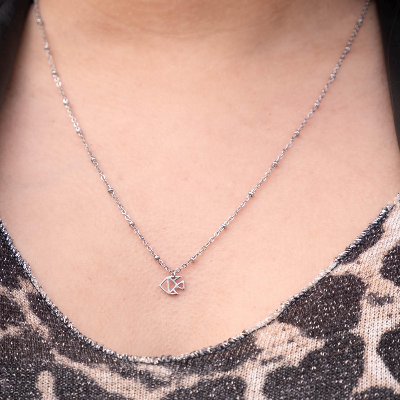 Vrouw met leopard top draagt sterrenbeeld vissen ketting