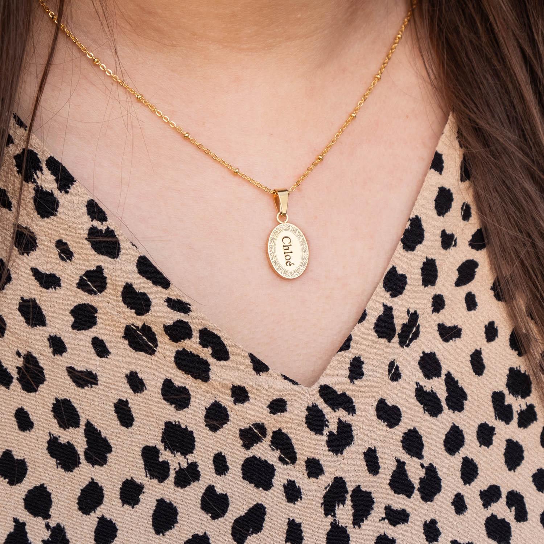 Meisje met leopard jurk draagt gouden naam ketting