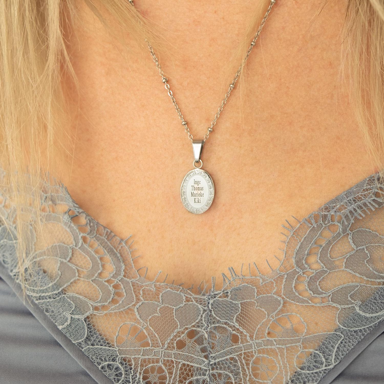 Vrouw draagt zilveren ketting met familie namen