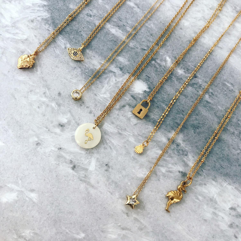 verschillende gouden kettingen op marmeren plaatje