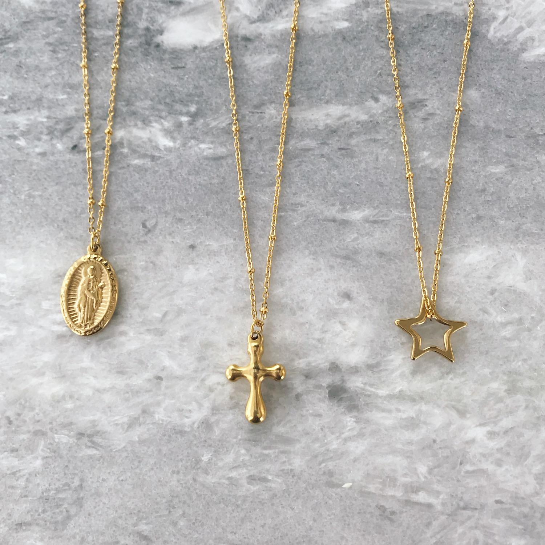 Drie gouden kettingen met hanger op grijze ondergrond