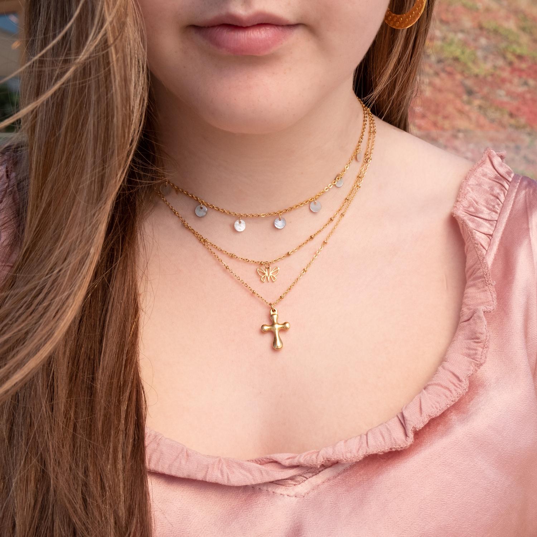 Meisje draagt drie gouden kettinkjes met hangertje