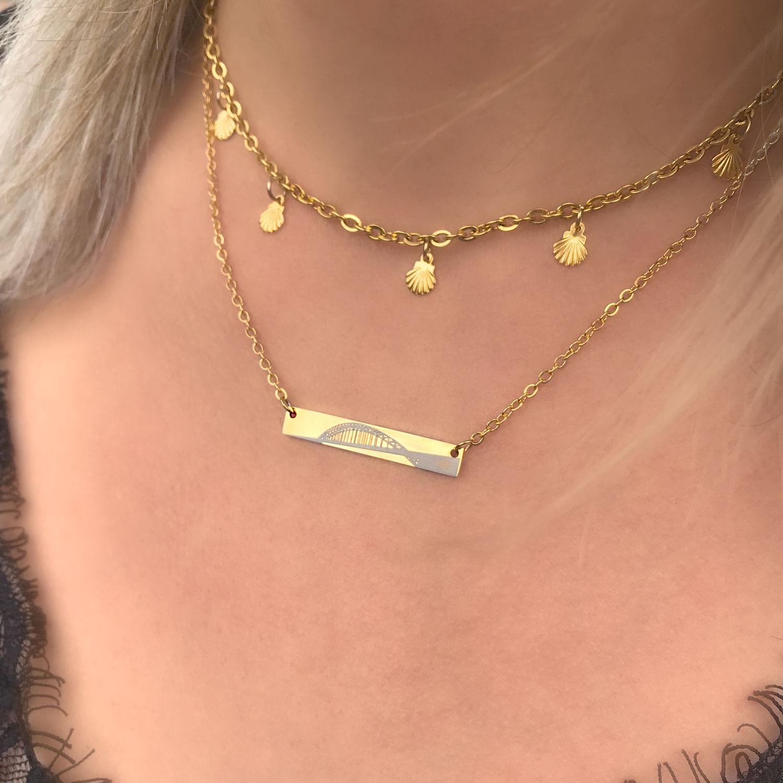 Vrouw draagt gouden ketting met waalburg om de hals