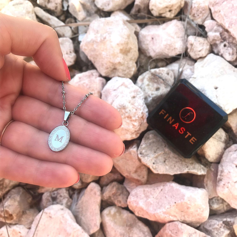 Zilveren ketting met bedel in de hand met sieradendoosje