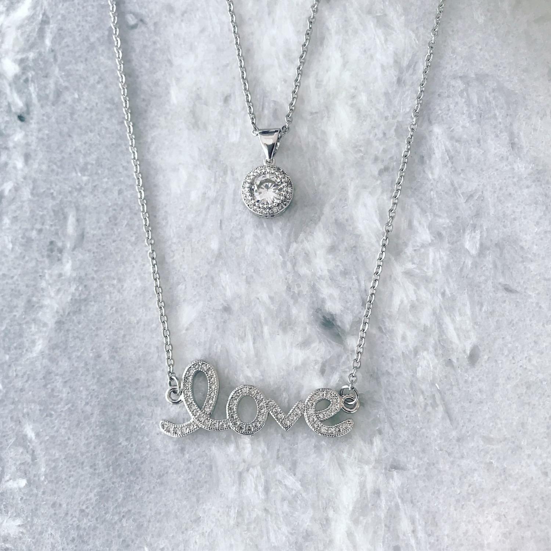 Twee zilveren kettingen met steentjes en quote