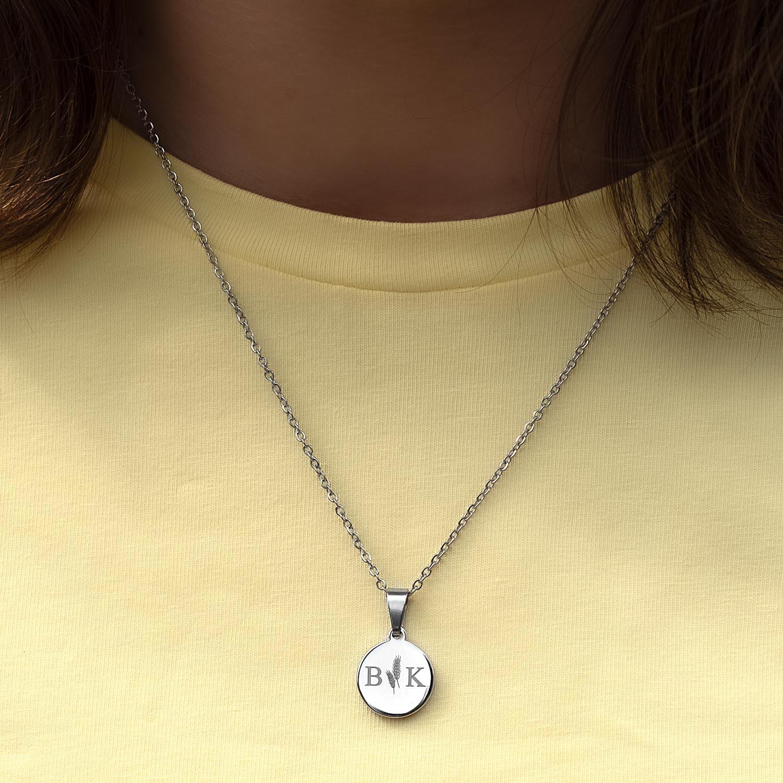 Zilveren ketting met twee initialen om de hals bij gele top