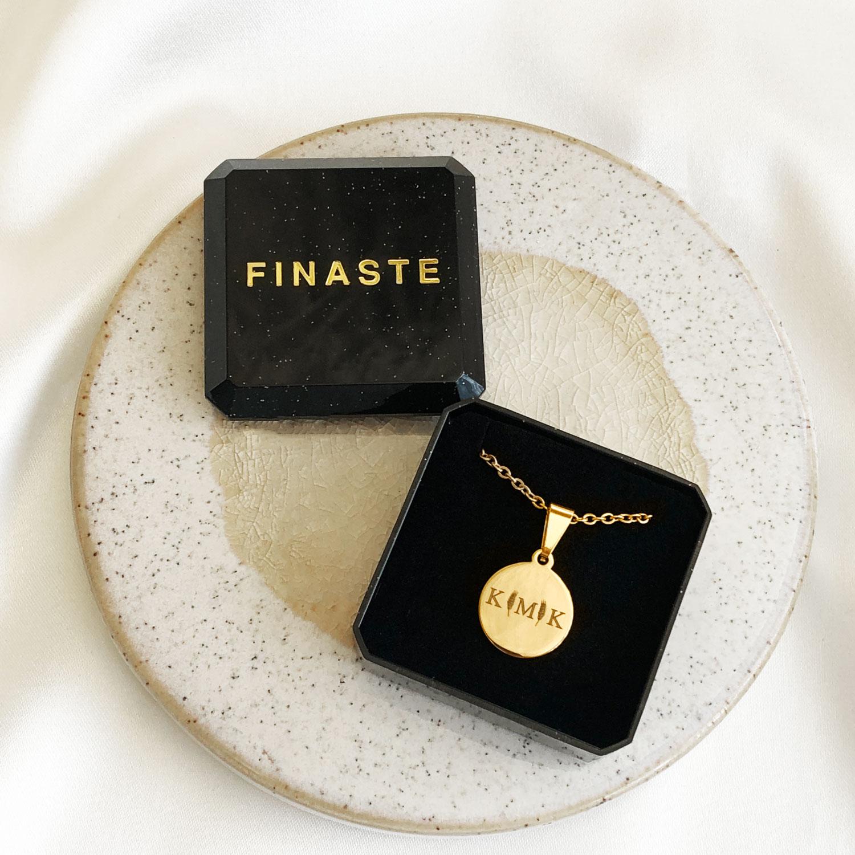 Mooie gouden ketting met drie letters in een sieradendoosje
