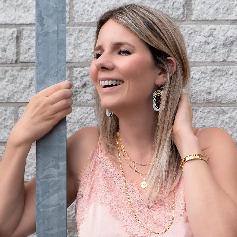 Vrouw draagt gouden kettingen om de hals met verschillende lagen