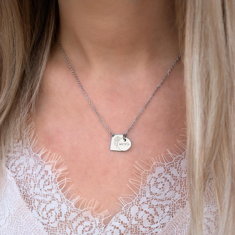 Zilveren ketting met initialen om de hals bij vrouw met blond haar