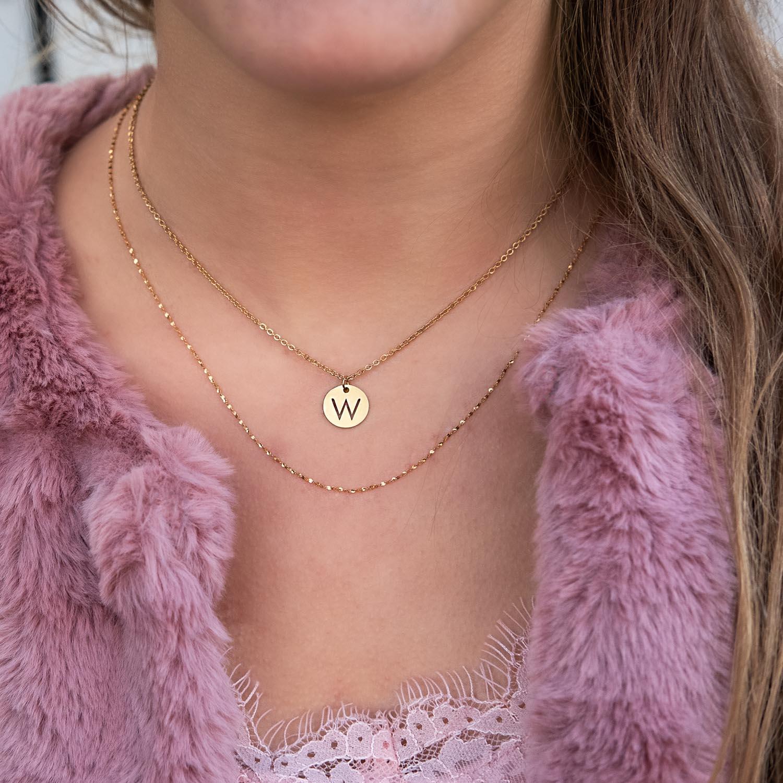 Roze bontjas samen met een initial coin ketting in het goud