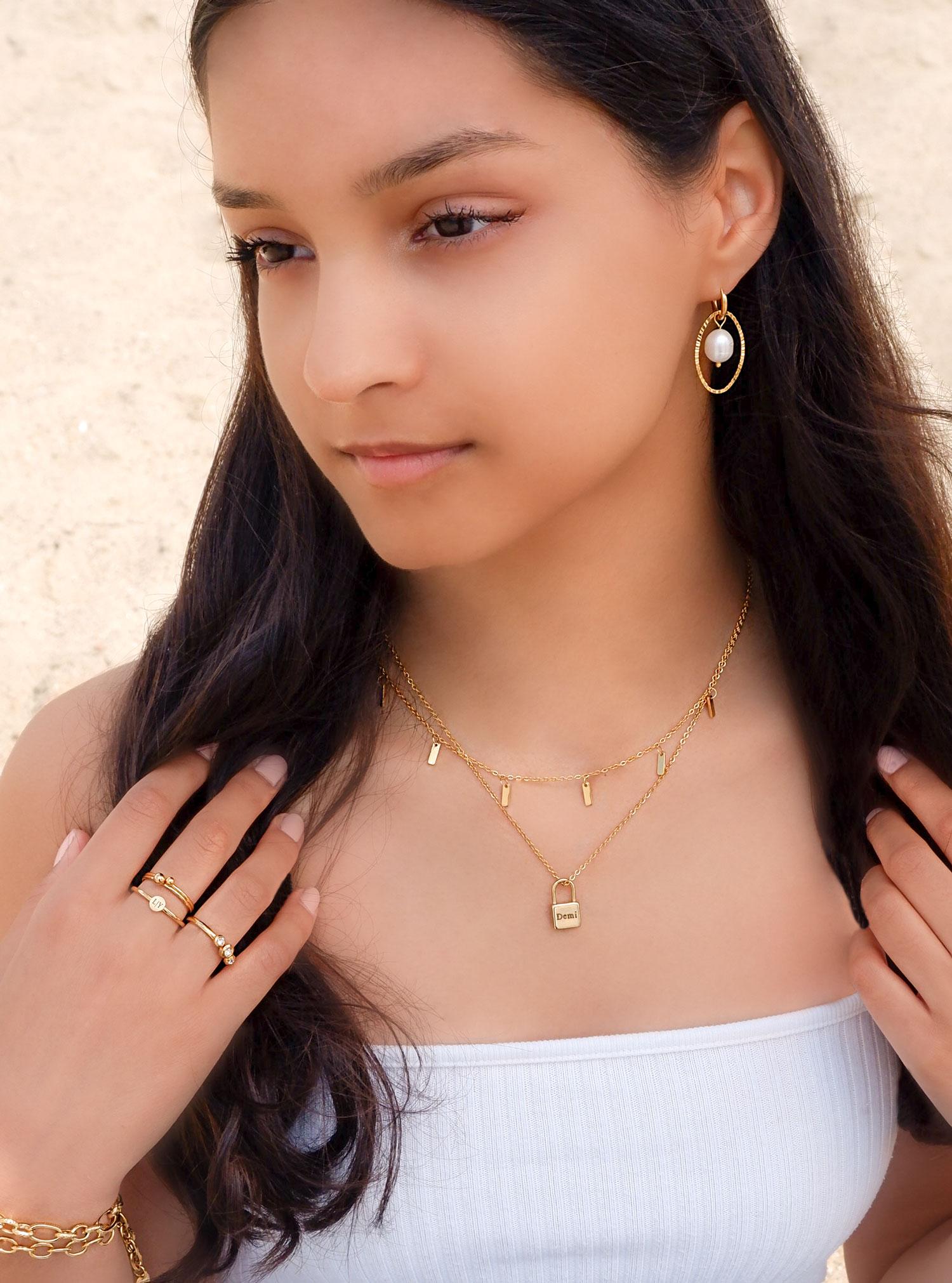 vrouw draagt gouden ketting met slotje voor om de hals