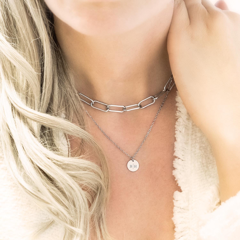 Vrouw draagt zilveren schakelketting samen met initialen