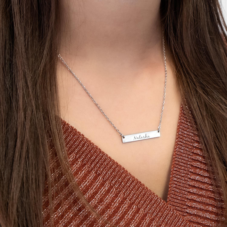 Vrouw draagt bar ketting met sierletters om de hals voor een party look