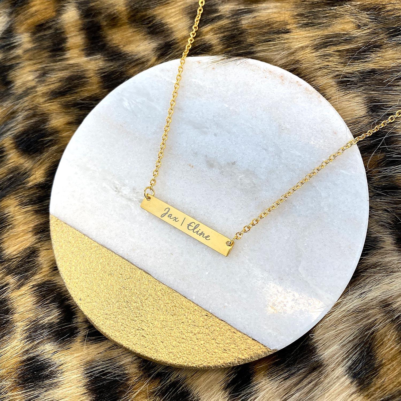 Mooie gouden bar ketting met sierletters op ketting gegraveerd