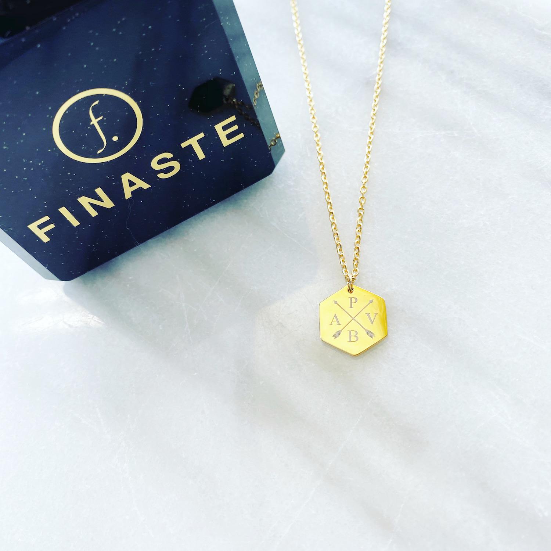 Gouden hanger ketting met 4 letters bij sieradendoosje op marmer