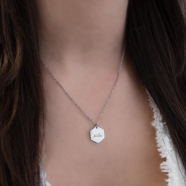 Mooie zilveren ketting met gravering om de hals met een wit jasje
