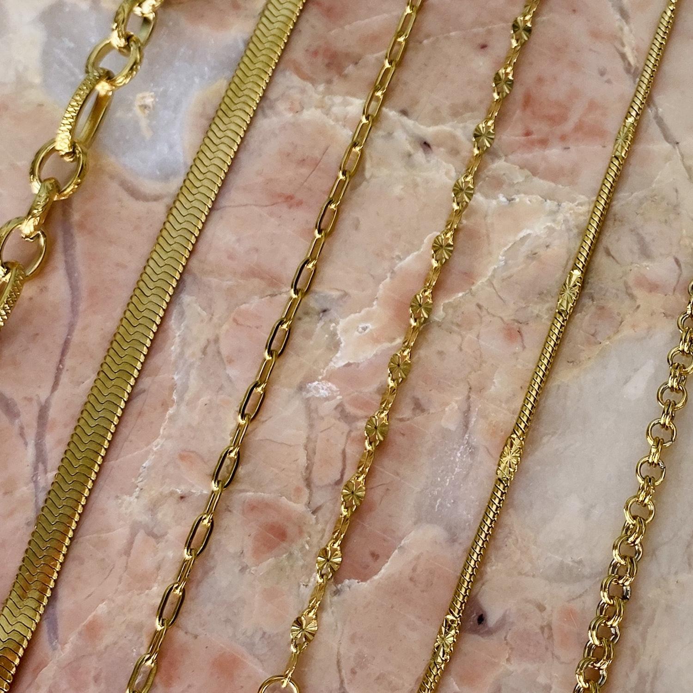 Gouden sieraden met schakels op marmer plaatje