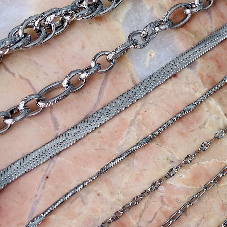 Zilveren schakelkettingen naast elkaar op roze marmer
