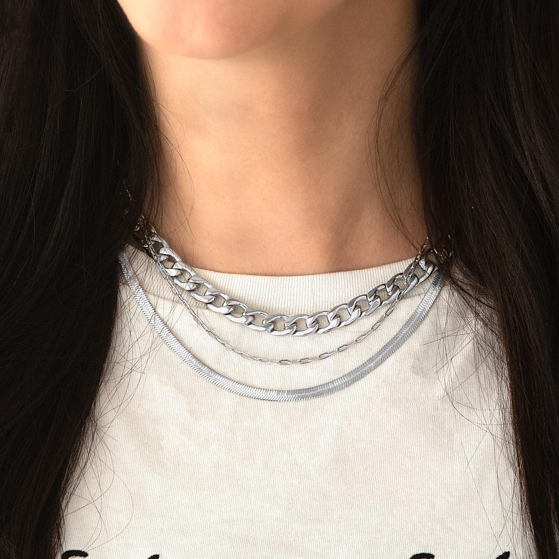 Drie zilveren kettingen bij witte top gecombineerd
