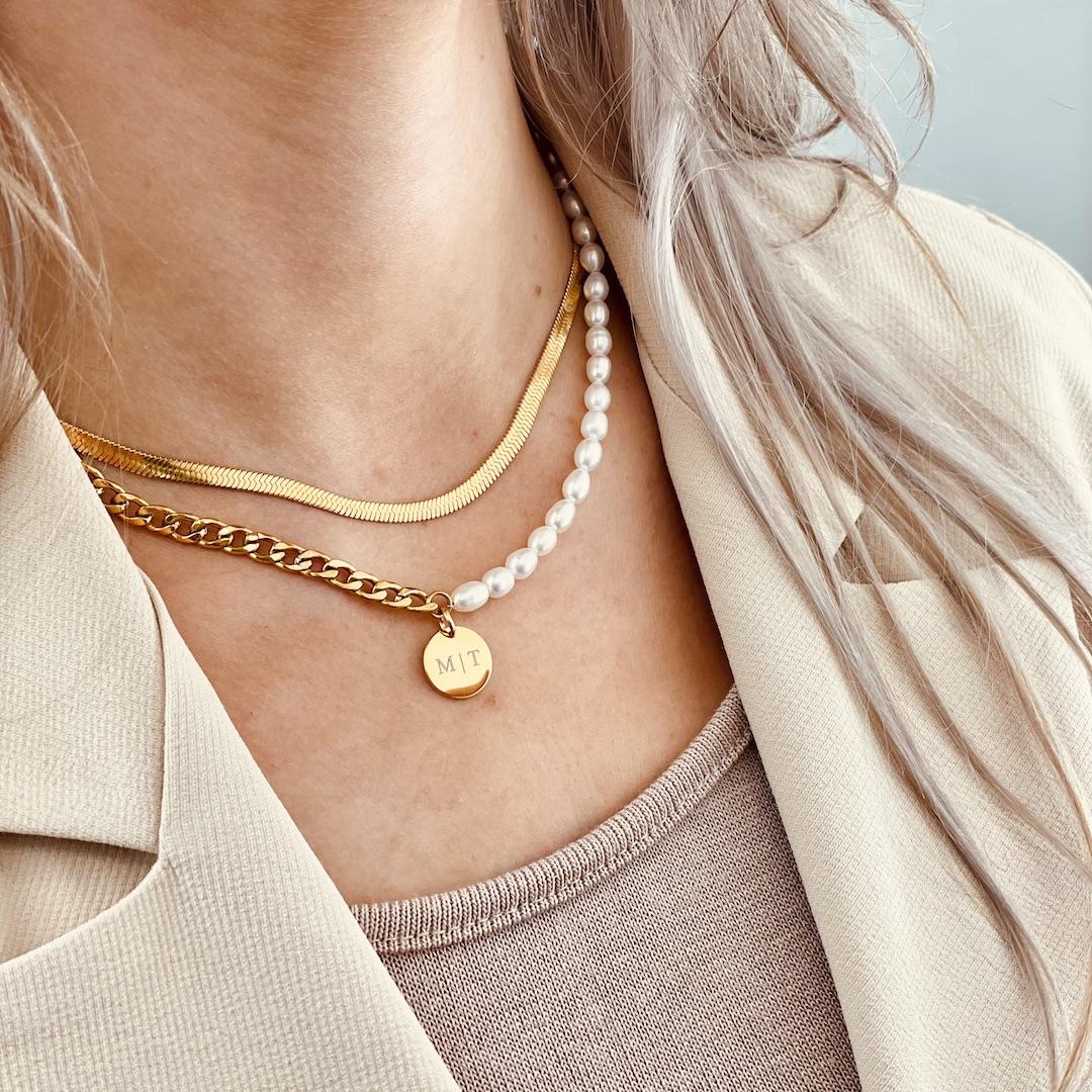 Blonde vrouw met necklace layer met parels en gravering goud