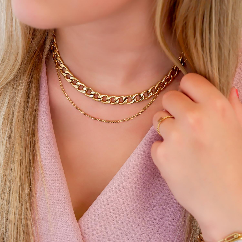 Twee gouden kettinkjes gecombineerd met elkaar met roze jurkje