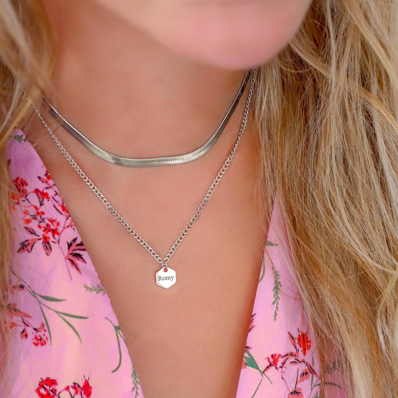 Meisje draagt hexagon ketting met gravering om hals