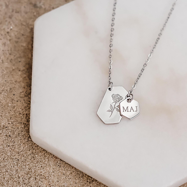 Roosjes ketting met hexagon hanger op marmeren steen
