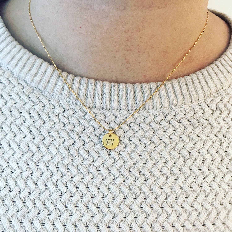 Gouden graveerbare ketting met muntje op witte trui