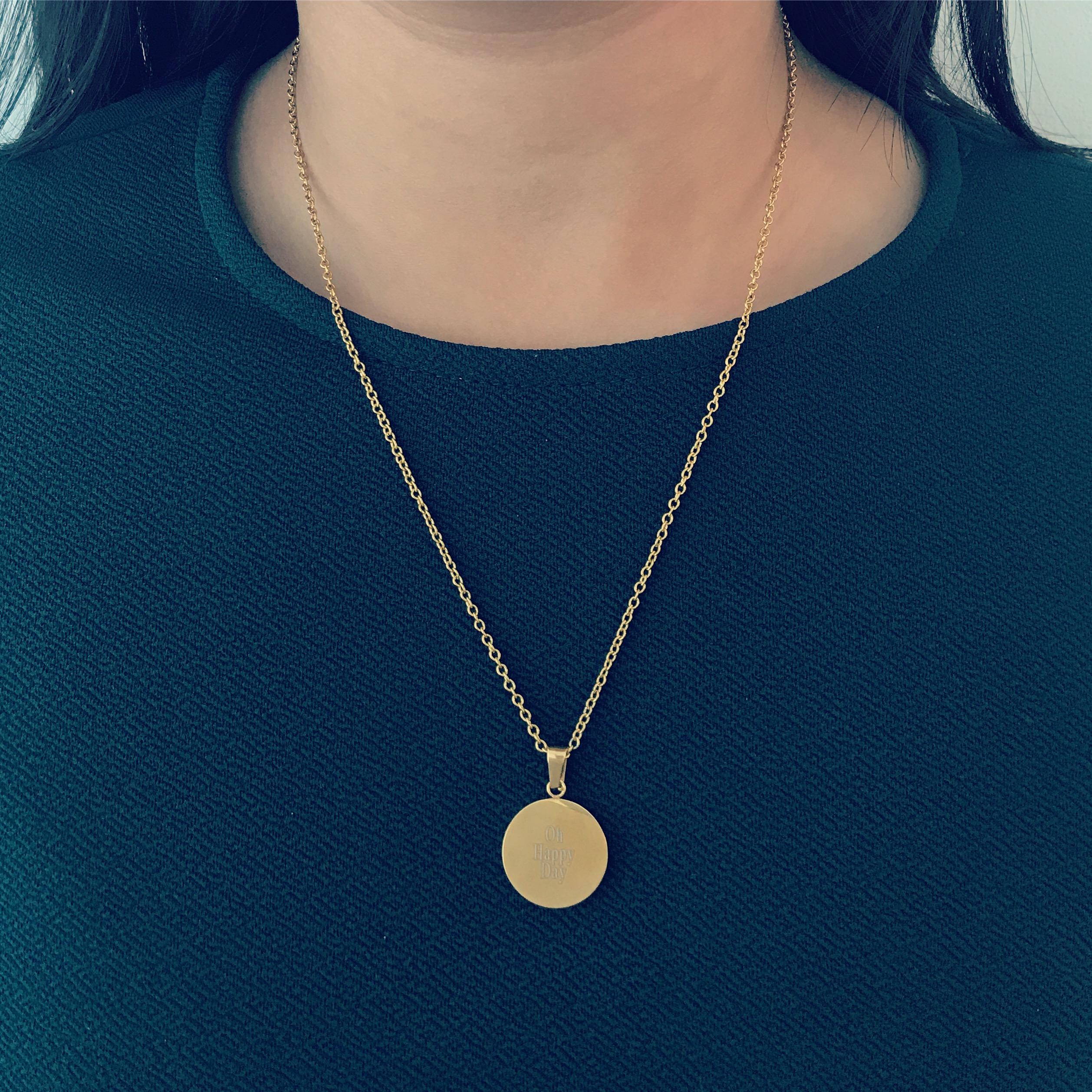 Ronde graveerbare gouden ketting bij meisje met donker haar