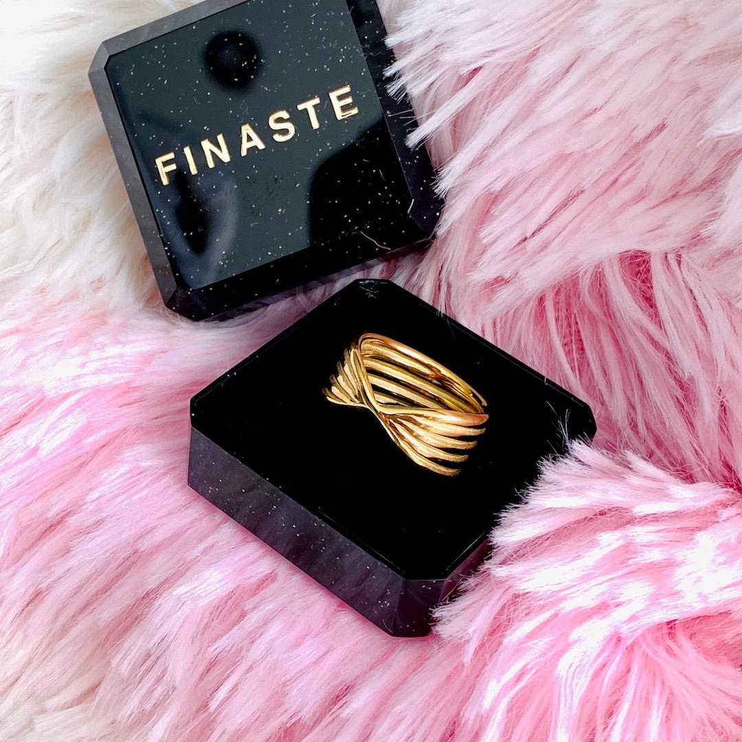 Gouden twist ring in sieradendoosje op roze ondergrond
