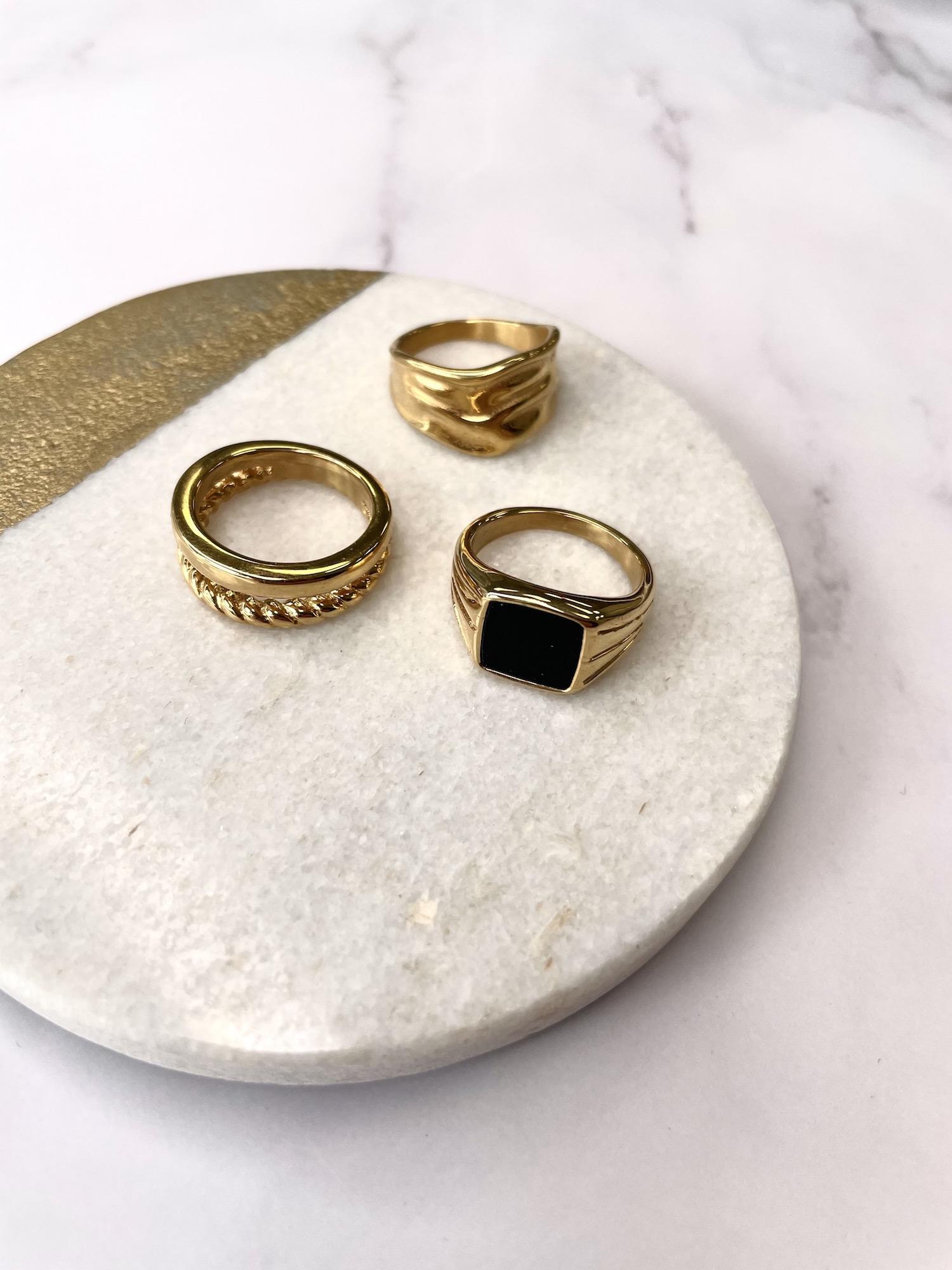 Mooie gouden chunky ringen op een marmeren achtergrond