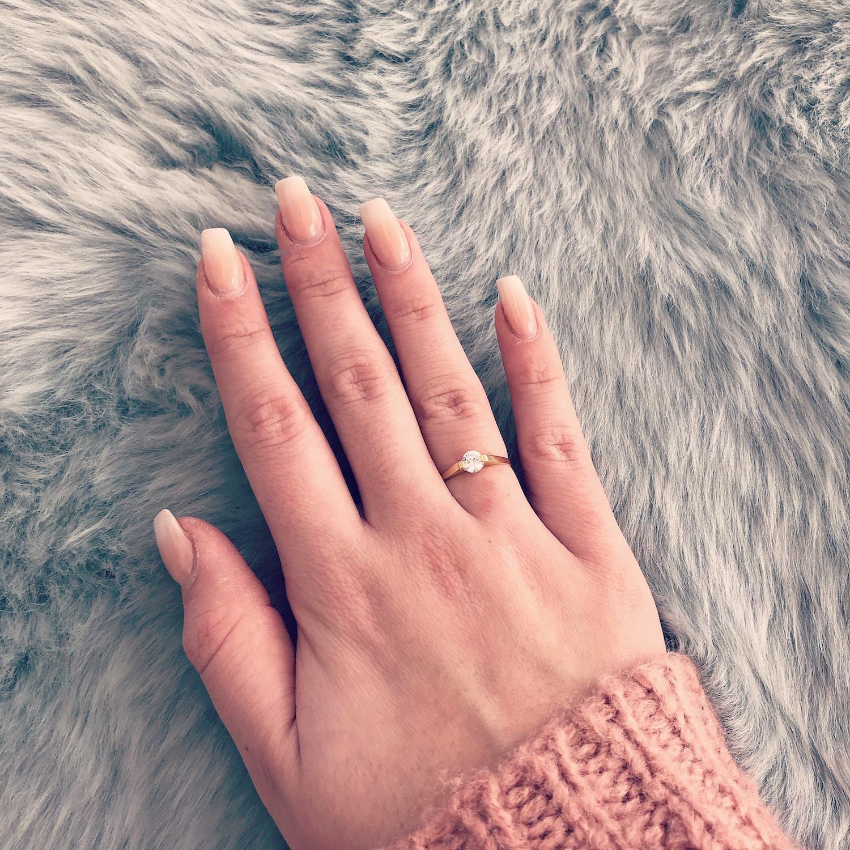 Hand met gouden ring met steentje