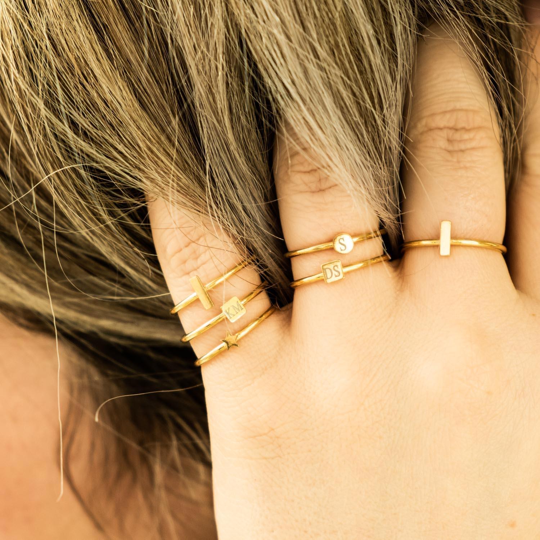 Minimalistische gouden ringen bij vrouw met blond haar