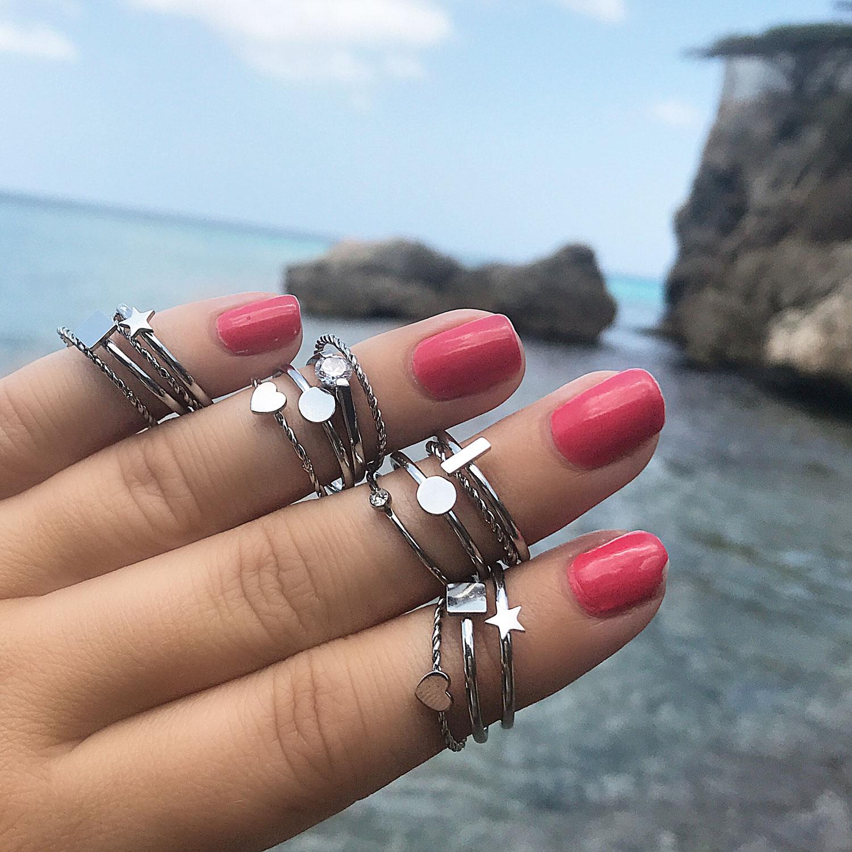 mooie zilveren ringen om de hand met roze nagellak