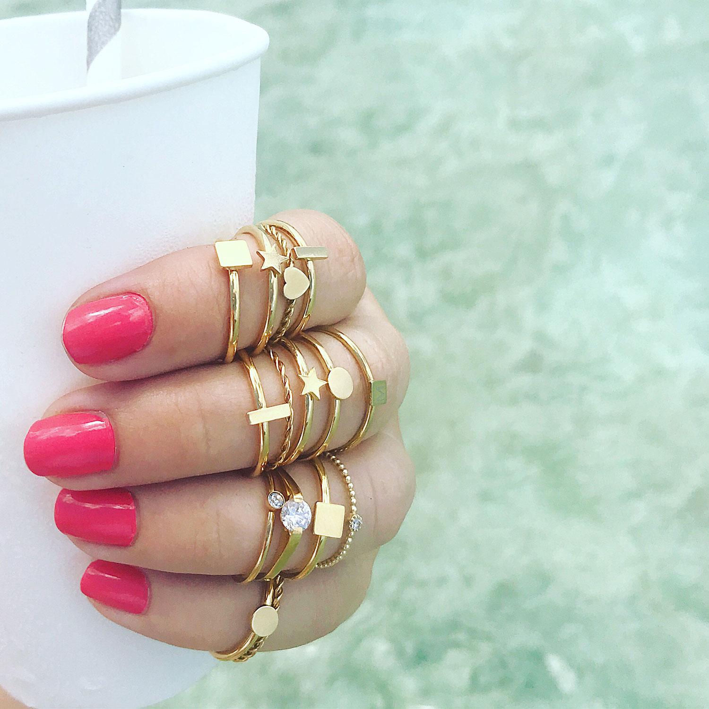 Verschillende ringen om de hand met roze nagellak