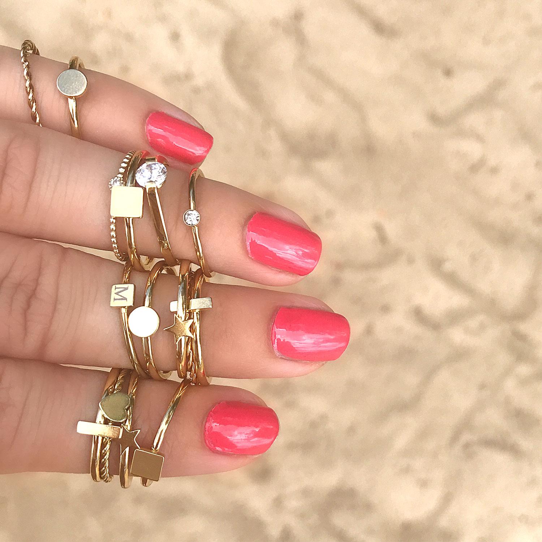 Verschillende gouden ringen om de hand met roze nagellak