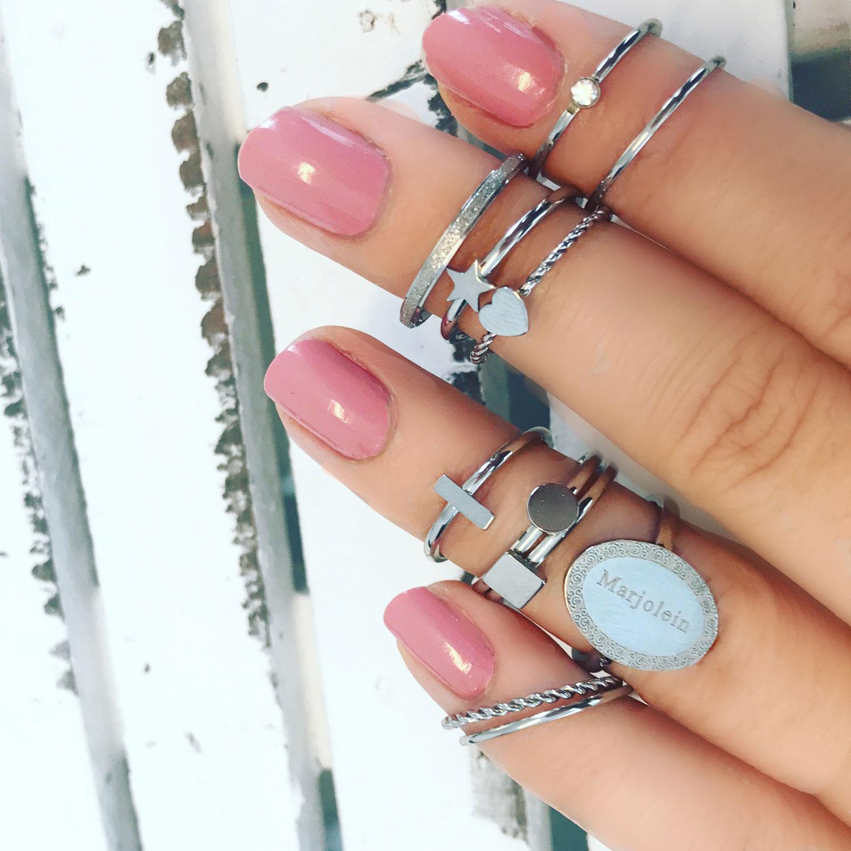 Zilveren ringen om een hand met roze nagellak