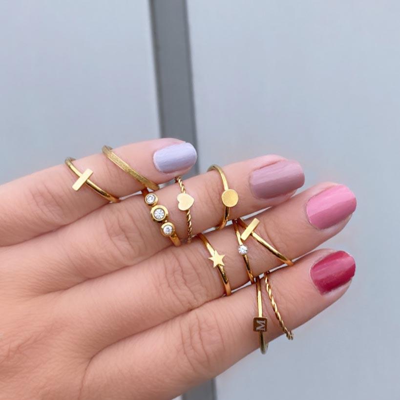Leuke gouden ringen om de hand met gekleurde nagels