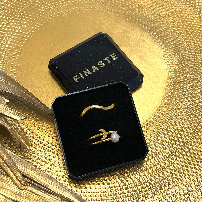 Golvende gouden ring in een sieradendoosje op een gouden plaatje