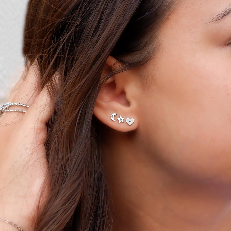 Trendy oorbellen met studs in het oor met een steentje