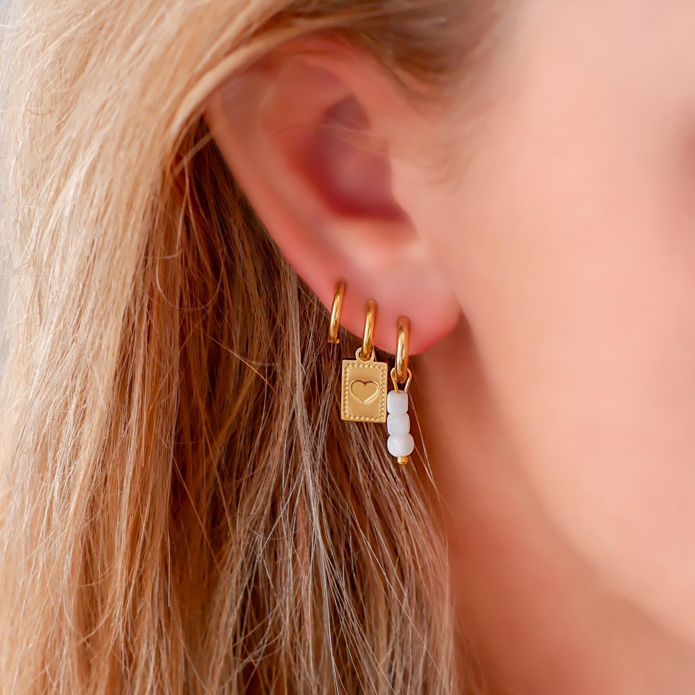 Trendy oorbel met hanger in het oor