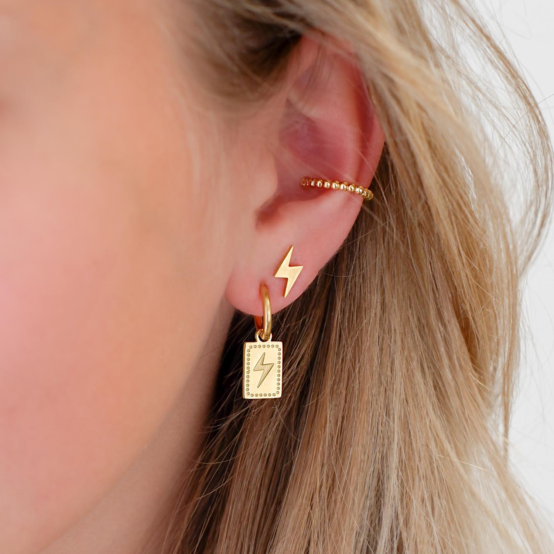 Gouden bliksem oorbellen in oor bij meisje