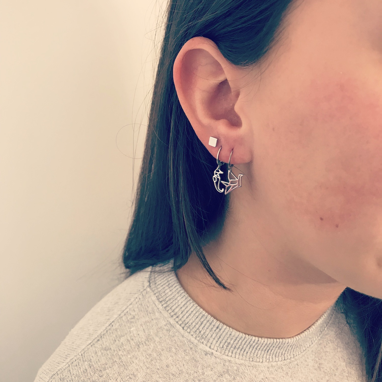 Vrouw draagt zilveren vierkante stud oorbellen van finaste