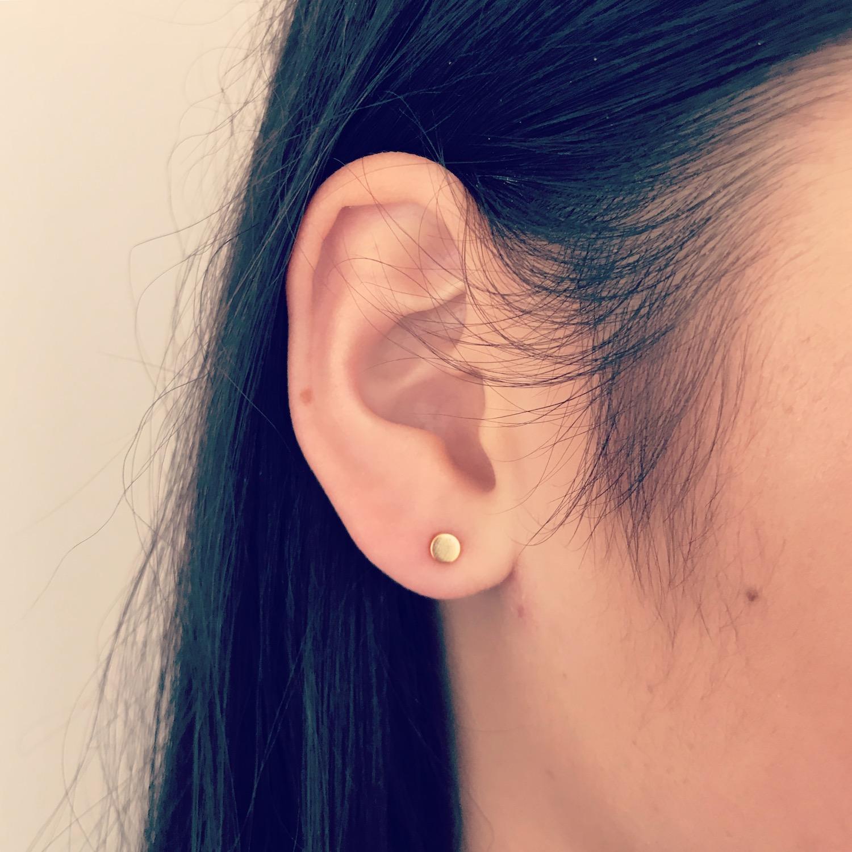 Gouden ronde stud oorbellen bij meisje met donker haar